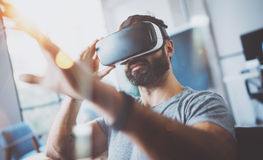 Primer del hombre joven barbudo que lleva gafas de la realidad virtual en estudio coworking moderno Smartphone usando con VR Imagen de archivo