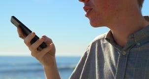 Primer del hombre joven que habla en el teléfono móvil 4k almacen de metraje de vídeo