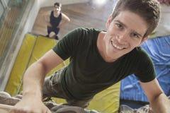 Primer del hombre joven sonriente que sube para arriba una pared que sube en un gimnasio que sube interior Foto de archivo libre de regalías