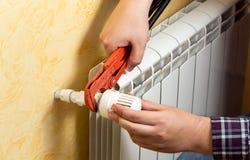 Primer del hombre que instala el radiador de la calefacción y que conecta la válvula fotografía de archivo