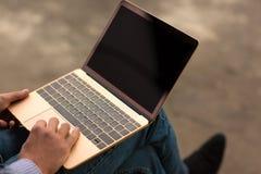 Primer del hombre que mecanografía Oficinista que se sienta con un nuevo ordenador portátil en el fondo urbano Concepto progresiv Imagen de archivo