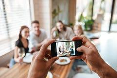 Primer del hombre que toma imágenes de amigos con el teléfono celular Imagen de archivo libre de regalías