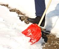 Primer del hombre que traspala nieve con la pala roja Imagen de archivo libre de regalías
