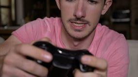 Primer del individuo enfocado competitivo que resuelve la sesión del videojuego que gana que controla los botones remotos en slow metrajes
