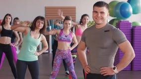 Primer del instructor masculino de la aptitud Él mira a un grupo de muchachas que entrenen en un gimnasio aerobio metrajes