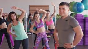 Primer del instructor masculino de la aptitud Él mira a un grupo de muchachas que entrenen en un gimnasio aerobio almacen de metraje de vídeo