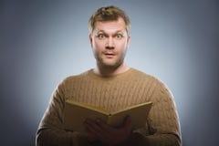 Primer del libro de lectura confuso del hombre contra fondo gris Fotos de archivo libres de regalías