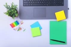 Primer del lugar de trabajo cómodo en oficina con el ordenador portátil, el cuaderno, los vidrios, la pluma y el otro equipo poni Fotografía de archivo libre de regalías