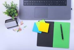Primer del lugar de trabajo cómodo en oficina con el ordenador portátil, el cuaderno, los vidrios, la pluma y el otro equipo poni Imágenes de archivo libres de regalías
