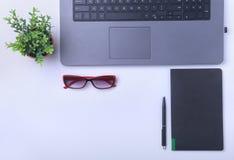Primer del lugar de trabajo cómodo en oficina con el ordenador portátil, el cuaderno, los vidrios, la pluma y el otro equipo poni Imagen de archivo libre de regalías