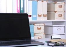 Primer del lugar de trabajo cómodo en oficina con el ordenador portátil, el ratón, el cuaderno, los vidrios, la pluma y el otro e Foto de archivo libre de regalías