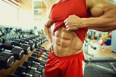 Primer del músculo en el vientre de un culturista en el gimnasio Foto de archivo