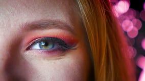 Primer del maquillaje femenino hermoso del ojo azul con las sombras rosadas y los brillos Expresión facial sonriente metrajes