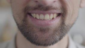 Primer del maxilar inferior de un hombre barbudo triste adulto que intenta sonreír con una sonrisa forzada Humor negativo, proble almacen de video