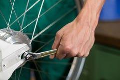 Primer del mecánico de la bicicleta con una llave Foto de archivo libre de regalías