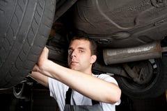 Primer del mecánico que trabaja debajo del coche Fotografía de archivo