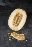 Primer del melón fresco y dulce Cantalupo amarillo en un fondo negro Postres sanos, con sabor a fruta Melón crudo por completo de foto de archivo libre de regalías