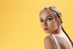 Primer del modelo de moda con el peinado fresco en fondo amarillo Imagen de archivo libre de regalías