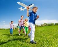 Primer del muchacho que detiene el aeroplano y a niños detrás Foto de archivo