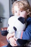 Primer del muchacho rubio precioso con el pelo rizado que abraza el juguete de la panda Imagen de archivo libre de regalías