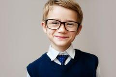 Primer del niño pequeño en uniforme escolar Colegial feliz que sonríe y que mira la cámara Foto de archivo