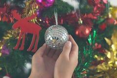 Primer del niño que cuelga la bola decorativa del juguete en el árbol de navidad Imágenes de archivo libres de regalías