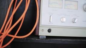 Primer del nuevo amplificador musical análogo gris con los cables anaranjados conectados almacen de video