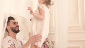 Primer del padre blando feliz y su pequeña de la hija que abrazan y que juegan en cama metrajes
