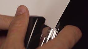 Primer del papeleo que sujeta con grapa masculino caucásico en la oficina almacen de metraje de vídeo