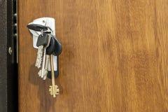 Primer del paquete de diversas llaves en agujero de la cerradura en textu de madera Imagen de archivo libre de regalías