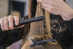 Primer del peluquero que endereza el pelo Fotografía de archivo