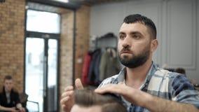 Primer del peluquero que hace que diseña con un hombre hermoso con una barba larga Manos del ` s del peluquero en el proceso de t metrajes