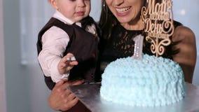 Primer del pequeño muchacho año que come la torta con sus manos y que alimenta a su madre almacen de metraje de vídeo
