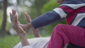 Primer del peque?o muchacho afroamericano lindo que se sienta encima de su madre irreconocible, de jugar, del tacto y de la tracc almacen de metraje de vídeo