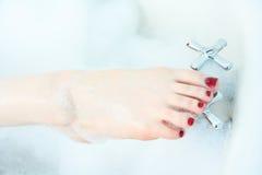 Primer del pie de la mujer en baño de burbuja. Fotos de archivo
