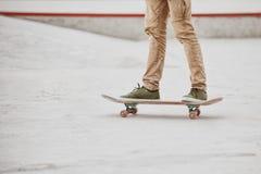 Primer del pie de los skateres mientras que patina en parque del patín Foto de archivo libre de regalías
