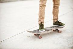 Primer del pie de los skateres mientras que patina en parque del patín Foto de archivo