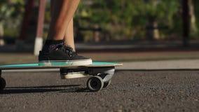 Primer del pie de un patinador en el tablero Longboard monta en el camino en la cámara lenta almacen de metraje de vídeo