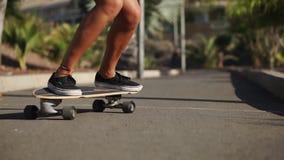 Primer del pie de un patinador en el tablero Longboard monta en el camino en la cámara lenta metrajes