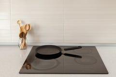 Primer del pote y de cucharas de madera en cocina moderna con la estufa de la inducción foto de archivo libre de regalías