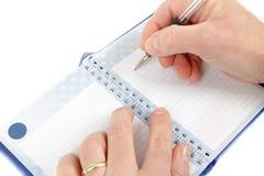 Primer del principio de la mano a escribir en notas Imagen de archivo
