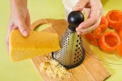 Primer del queso grating del cocinero. imagen de archivo