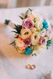 Primer del ramo nupcial hermoso con los anillos de bodas de oro de los pares Fotografía de archivo libre de regalías
