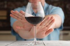 Primer del rechazo masculino de la mano al vidrio de vino ofrecido fotografía de archivo