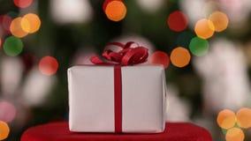 Primer del regalo de la Navidad como resbala delante de árbol de Navidad metrajes