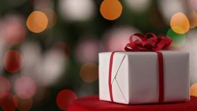Primer del regalo de Navidad contra árbol adornado de Navidad almacen de video