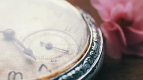 Primer del reloj de bolsillo al lado de una flor y de un paso del tiempo violetas suavemente rosados almacen de metraje de vídeo