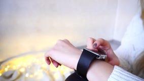 Primer del reloj elegante en la mano del ` s de la muchacha, que utiliza el artilugio para la correspondencia en sitio brillante  metrajes