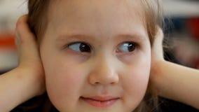 Primer del retrato de una muchacha del niño que mira en la cámara y la sonrisa almacen de metraje de vídeo