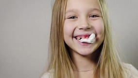 Primer del retrato de una muchacha sonriente linda, niño con una servilleta blanca en su boca, gomas que sangran, mandíbula Pérdi metrajes